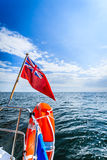 Blue sea. View from deck of yacht sailboat british flag lifebuoy. Travel. Stock Photo