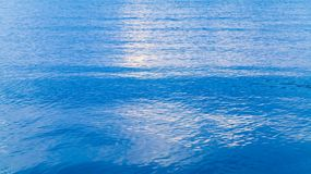 Blue sea water background photo texture. With soft ripple and cloudy sky reflection royalty free stock photography