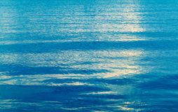 Blue sea water background texture. With soft ripple and cloudy sky reflection stock photography