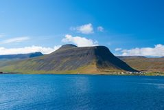 Blue sea water on mountain landscape in isafjordur, iceland. Hilly coastline on sunny blue sky. Summer vacation on. Scandinavian island. Discover wild nature Royalty Free Stock Photos