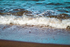 Blue sea water over ginger brown sand beach. Relaxing sea wave surf over seashore. Volcanic beach of tropical paradise. Idyllic seascape for summer vacation Stock Photography