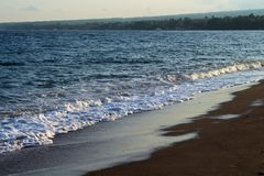 Blue sea water over volcanic sand beach. Relaxing sea wave surf over seashore. Stock Photos