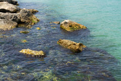 Blue sea water on rocky shore Stock Photography