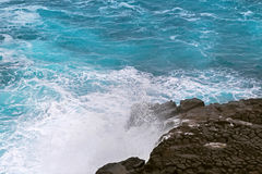 Blue sea water splashing volcanic rock at blowhole at Cape Bridg Stock Photo