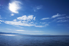 Blue sea water surface cloudy sky. Blue sea water surface white clouds Royalty Free Stock Photography