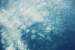 Blue sea water with underwater stones Stock Image