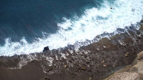 Blue sea waves beat against the stone beach. Slowmotion stock footage