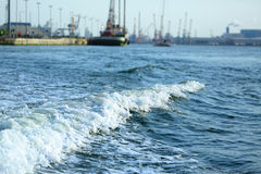 Blue sea with waves and foam against the port Stock Images