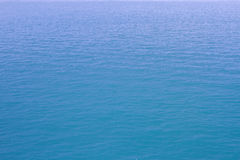 Blue sea waves surface soft and calm with blue sky background Stock Photos