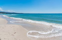 Blue sea and white sand in Alghero Stock Image