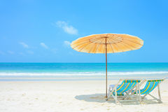 Blue sea and white sand beach with beach chairs and parasol Stock Photos