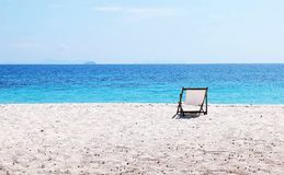 Blue sea and white sand with beach chairs stock photo