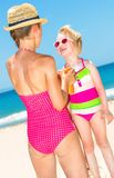 Happy modern mother and child on beach applying sun screen Stock Photography