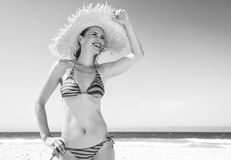 Woman in beach straw hat on seacoast looking into distance. Blue sea, white sand paradise. smiling modern woman in beachwear and straw hat on the seacoast stock photo