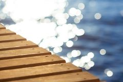 Blue sea and wooden pier. Wooden pier stretching into the blue sea. Shallow depth of field Royalty Free Stock Images