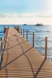 Blue sea and wooden pier. Wooden pier stretching into the blue sea. Shallow depth of field Stock Images
