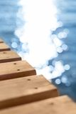 Blue sea and wooden pier. Wooden pier stretching into the blue sea. Shallow depth of field Stock Photos