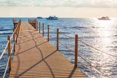 Blue sea and wooden pier. Wooden pier stretching into the blue sea. Shallow depth of field Stock Photography