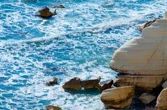 Blue sea, yellow rock Royalty Free Stock Photography
