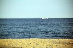 Blue sea, yellow sand, white ship Stock Photography
