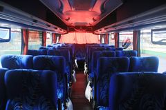 Blue seats with plastic trash bags at the side in a bus with red curtains from south america stock photo