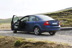 Blue sedan car from back, open door. Blue sedan car with driver door open is standing on road side on mountain plateau royalty free stock photo