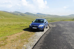 Blue sedan car on mountain plateau. Blue sedan car parked on road side on mountain plateau. Nice green peaks at the back royalty free stock images