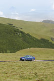 Blue sedan car on mountain road. Blue sedan car on mountain plateau road stock photo