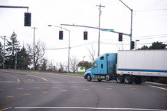 Blue semi truck and trailer on road with traffic lights Royalty Free Stock Photo