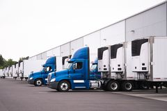 Blue semi trucks and semi trailers stand in row hardly near the. A day cab big rigs semi trucks with a reefer trailers stand near the gate of the warehouse next Stock Photo