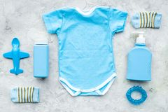 Blue set for newborn boy. Baby bodysuit, socks, airplan toy, oap and powder on grey background top view.  Stock Image