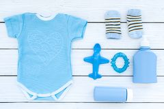 Blue set for newborn boy. Baby bodysuit, socks, airplan toy, oap and powder on white wooden background top view.  Royalty Free Stock Images