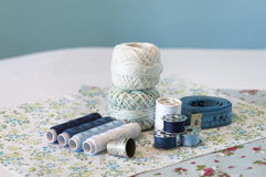 Blue sewing items. With spools, threads, a measuring tape, and a thimble on some fabrics with flowers royalty free stock photo