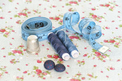 Blue sewing items. With various buttons, spools, threads, a measuring tape, a thimble and a needle on on a fabric with flowers royalty free stock images