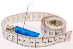 Needle, thread, measuring tape and thimble as a symbol for tailoring stock images