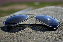 Blue Shade Sunglass. In focus on ground Royalty Free Stock Photo