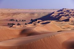 Camping in oasis in the desert. Blue shadows and sand waves horizon stock photography