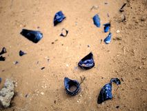 Blue shattered glass on sandy dirt backdrop. Blue shattered glass on sandy dirt Stock Photo