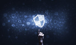 Blue shield icon as symbol of access protection on dark background Royalty Free Stock Images