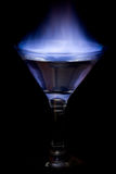 Blue shine. Burning of a liquid in a glass on a black background Royalty Free Stock Photo