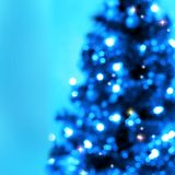 Blue shining Christmas tree. On a blue background soft image of Christmas tree decorated with garlands. There is plenty of space for text and additional elements Stock Photography