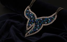 37be52061c4d71 Blue shiny butterfly shape necklace on velvet background. Blue shiny  butterfly necklace with gem stones