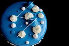 Blue shiny cake with white chocolate ganache and mirror glaze isolated on black background stock image