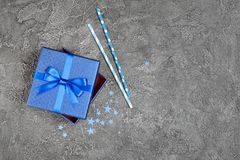 Blue shiny classic gift box with satin bow and paper cocktail straws with confetti in the shape of stars as attributes of party royalty free stock photos