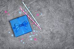 Blue shiny classic gift box with satin bow and paper cocktail straws with confetti in the shape of stars as attributes of party stock photos