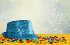 Blue shiny party Hat next to colorful candies stock photos