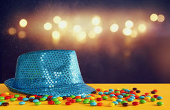 Blue shiny party Hat next to colorful candies royalty free stock photos