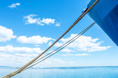 Blue ship`s nose on a blue sky background. Ship`s ropes. Beautiful clouds. Lighthouse on the horizon. Royalty Free Stock Photo
