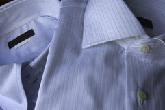 Blue shirt. In the first line, white shirt with blue stripes, Background, blue shirt of cotton type oxford Royalty Free Stock Image