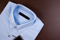 Blue shirt with black blank price tag. royalty free stock images